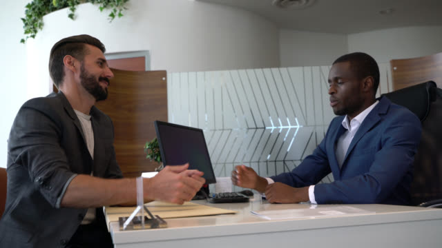 cheerful black salesman handing the keys to a car to handsome caucasian customer at a car dealership - contract stock videos & royalty-free footage
