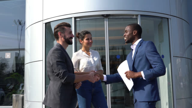 cheerful black salesman handing the keys to customer couple at a car dealership shaking hands all smiling - customer stock videos & royalty-free footage