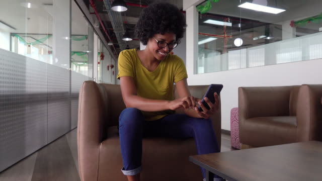 cheerful black woman at the office relaxing on couch checking her social media smiling - coworking stock videos & royalty-free footage
