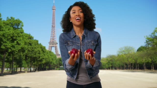 vídeos de stock e filmes b-roll de cheerful black woman juggling apples in front of eiffel tower in paris - ensolarado