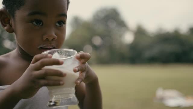 glad pojke dricker mjölk i parken - ungdomskultur bildbanksvideor och videomaterial från bakom kulisserna