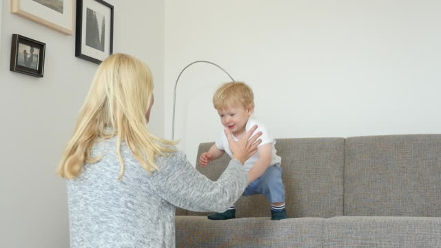 Cheerful boy jumping towards mother at home