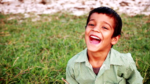 cheerful boy sitting in the field and studying outdoor portrait - primary school child stock videos and b-roll footage