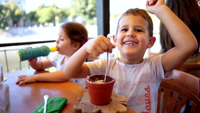 cheerful brother and sister spending time eating ice cream at a cafe - spoon stock videos & royalty-free footage