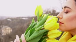 Cheerful brunette woman enjoying smell of yellow tulips given by beloved man