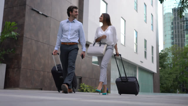 cheerful business couple walking towards hotel each pulling their wheeled luggage while talking - wheeled luggage stock videos & royalty-free footage