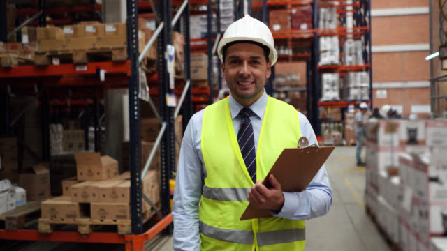 cheerful business man at a distribution warehouse holding a clipboard facing camera smiling - world trade organisation stock videos & royalty-free footage