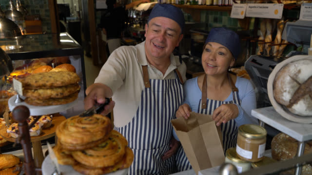 cheerful business owners of a bakery preparing a take out order adding cookies and pastries to a paper bag - paper bag stock videos & royalty-free footage