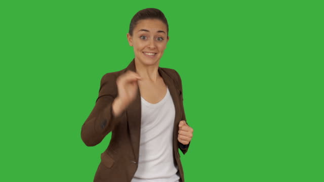 Cheerful business woman playing rock paper scissors on a green background