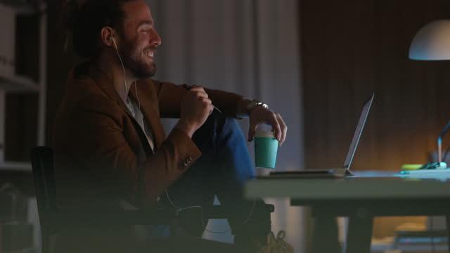 fröhlicher geschäftsmann sitzt im büro tragen kopfhörer und halten kaffeetasse, während sie einen videoanruf auf seinem laptop - getränk stock-videos und b-roll-filmmaterial