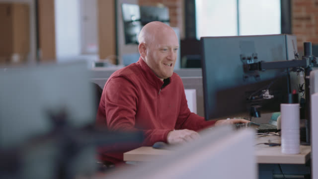 cheerful businessman laughs as he types on his computer at his office desk - using computer stock videos & royalty-free footage