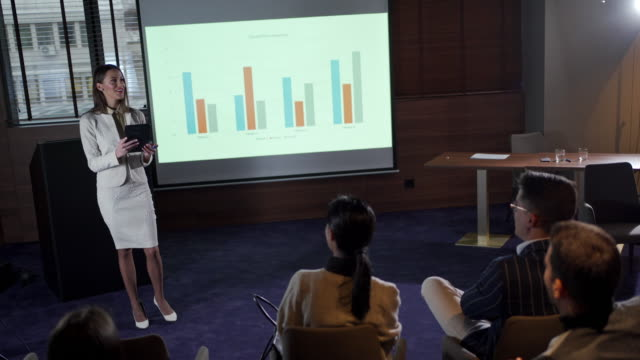 stockvideo's en b-roll-footage met vrolijke onderneemster die een bedrijfspresentatie in een conferentieruimte houdt - diavoorstelling