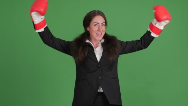 cheerful businesswoman in boxing gloves on green background