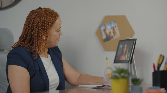 cheerful businesswoman jots down notes as she holds a video conference with her fellow coworker - wilmington north carolina stock videos & royalty-free footage