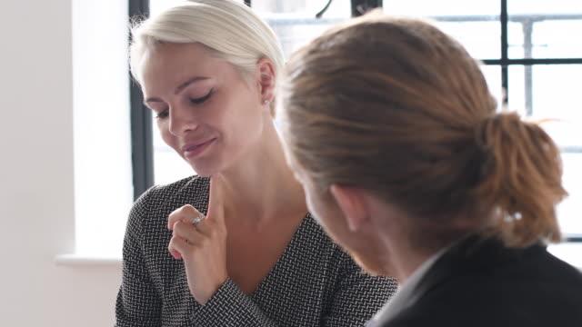 fröhliche geschäftsfrau im gespräch mit jungen mann im büro und ihr haar einstellen - kurzes haar stock-videos und b-roll-filmmaterial