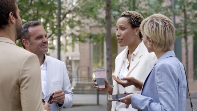 vidéos et rushes de femme d'affaires gaie parlant avec des collègues - déjeuner