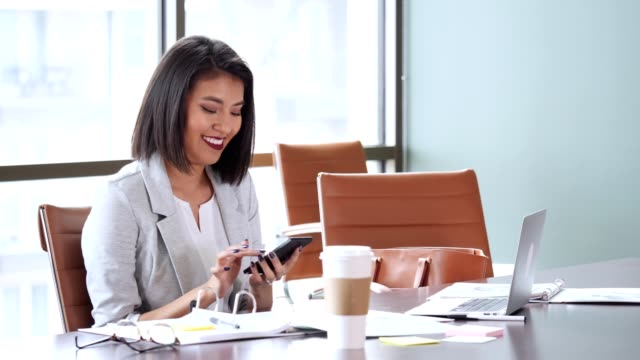 cheerful businesswoman uses smartphone while working - stationary stock videos & royalty-free footage