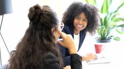 Cheerful businesswomen talking at desk in office