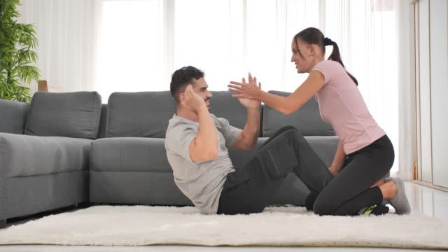 cheerful caucasian couples stretching muscles doing situps training in living room,training at home.home exercise - bodyweight training stock videos & royalty-free footage