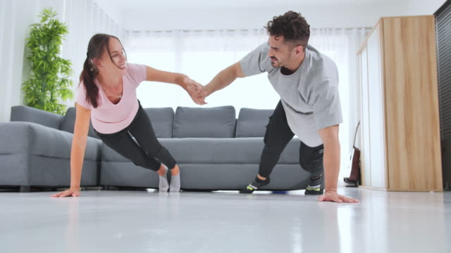 cheerful caucasian couples stretching muscles,training at home. - bodyweight training stock videos & royalty-free footage