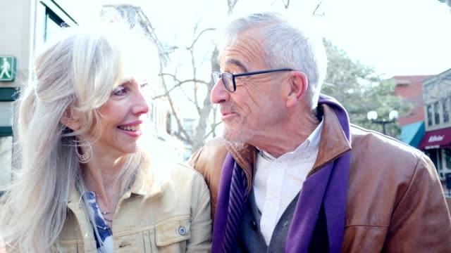 cheerful caucasian senior man and woman enjoy talking together outdoors on a beautiful day - shrugging stock videos and b-roll footage