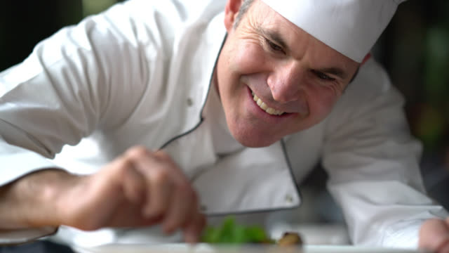Cheerful chef decorating a plate looking very happy