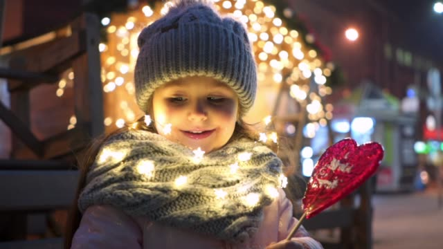 cheerful child enjoying a heart shaped lollipop during christmas - christmas market stock videos & royalty-free footage