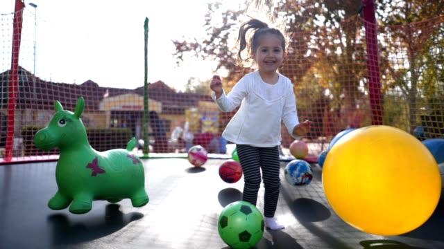 stockvideo's en b-roll-footage met vrolijk kind genieten van een zonnige dag springen op een trampoline - trampoline