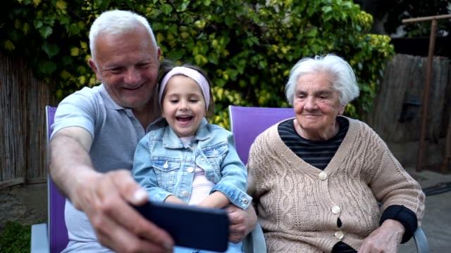 vídeos de stock e filmes b-roll de cheerful child having fun with grandparents in a back yard - família de várias gerações