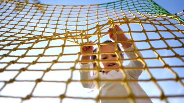 cheerful child holding on to a net while jumping on a trampoline - playground stock videos & royalty-free footage