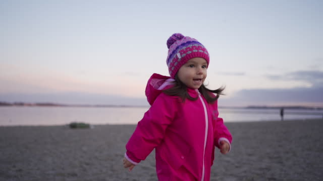 cheerful child in ski-wear running on a sandy beach in winter - skiwear stock videos & royalty-free footage