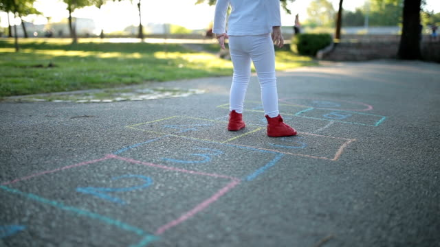 Cheerful child playing hopscotch in the park