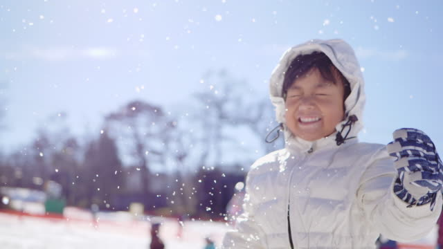 cheerful child playing in the snow - coat garment stock videos & royalty-free footage