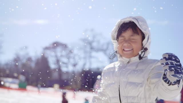 vidéos et rushes de enfant gai jouant dans la neige - manteau et veste
