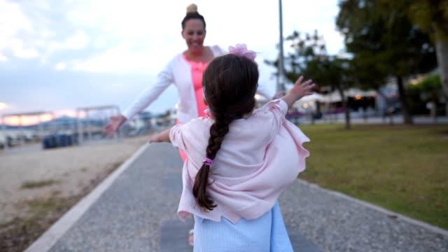 vídeos y material grabado en eventos de stock de niño alegre corriendo al abrazo de su madre - brazos estirados