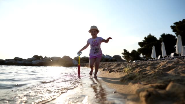 cheerful child with a water squirt gun running on the beach - sea squirt stock videos & royalty-free footage
