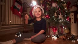 Cheerful child with Santa hat having fun with sparklers