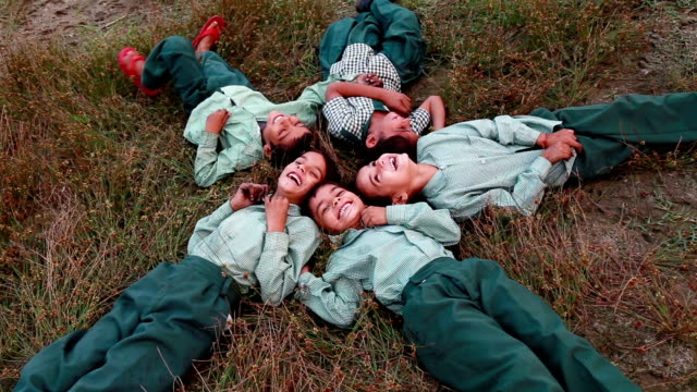 cheerful children lying dawn on grass - primary school child stock videos and b-roll footage