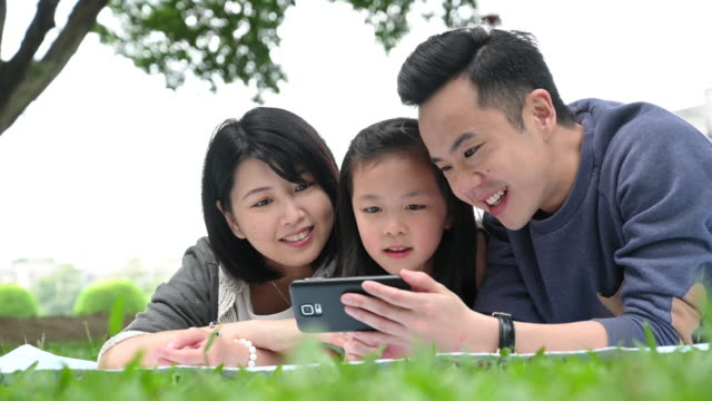 cheerful chinese family looking at smartphone - taipei stock videos & royalty-free footage
