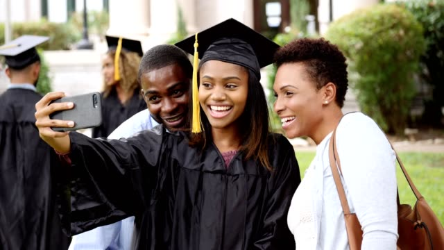 cheerful college grad takes selfie with parents - graduation stock videos & royalty-free footage
