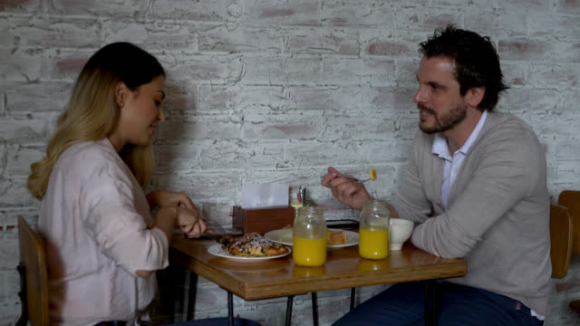 cheerful couple at a cafe enjoying breakfast while talking - french food stock videos & royalty-free footage