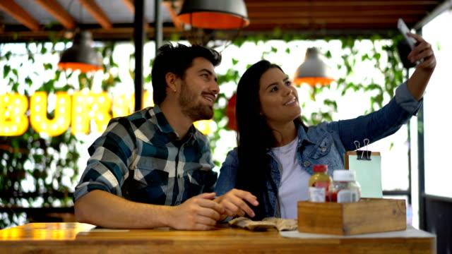 スマート フォンを笑顔で selfie を取るレストランで陽気なカップル