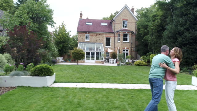 Cheerful couple embracing in garden and looking at their large detached house