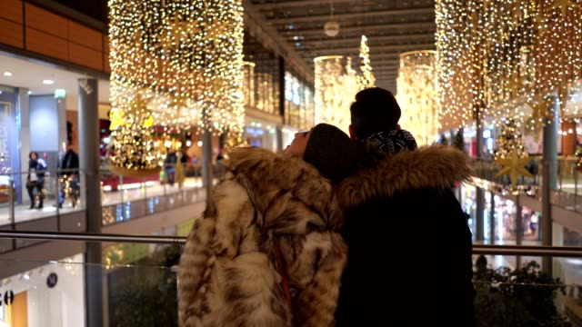 cheerful couple enjoying christmas decoration at a mall - romance stock videos & royalty-free footage