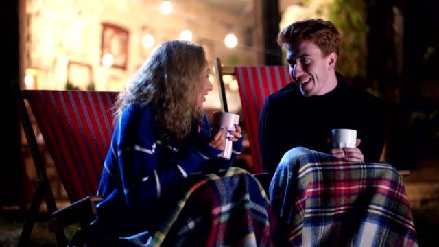 fröhliches paar genießen ihre zeit in der nacht in einem vorgarten - vorlesen stock-videos und b-roll-filmmaterial