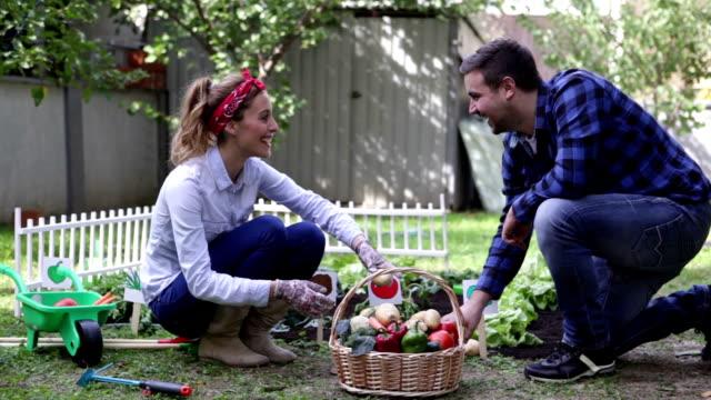 HD: Cheerful Couple Gardening in vegetable garden.
