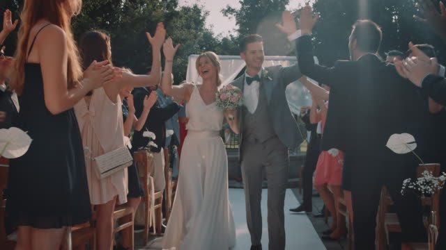 cheerful couple giving high-five to wedding guests - young men stock videos & royalty-free footage