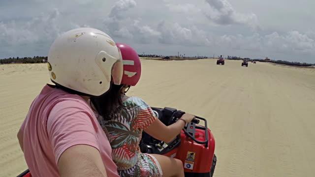 cheerful couple having fun on a quad bike. - quadbike stock videos & royalty-free footage