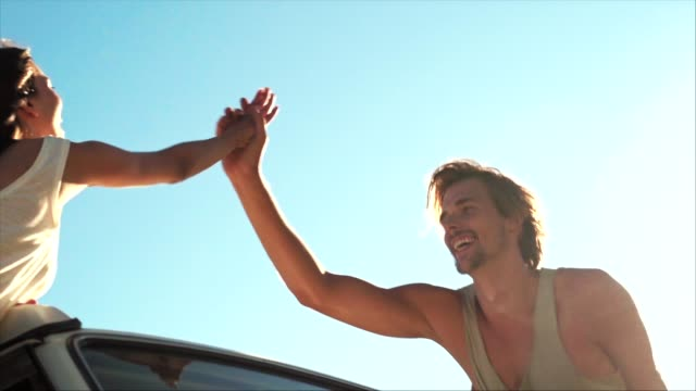 cheerful couple high-fiving during road trip - adventure stock videos & royalty-free footage
