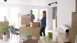 Cheerful couple moving in the new apartment
